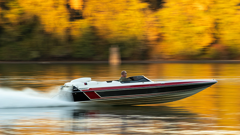 Man driving motorboat in fall